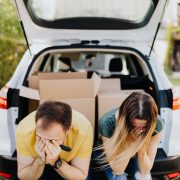 tired couple sitting on car luggage boot